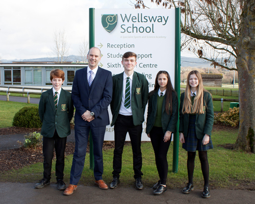 The Head of Wellsways School, Matthew Woodville outside the school with three students following their successful Ofsted report, January 2018